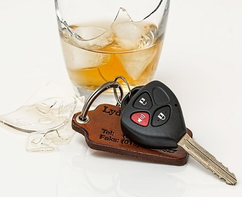 a picture of a set of keys sitting next to an alcoholic beverage
